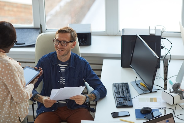 Portrait of smiling businessman talking to assistant while working at desk in modern office, copy space