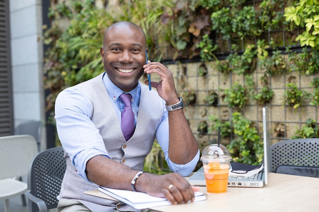 Portrait of a smiling businessman talking through his smartphone