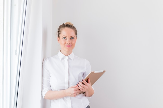 Portrait of smiling businesswoman holding laptop leaning on wall