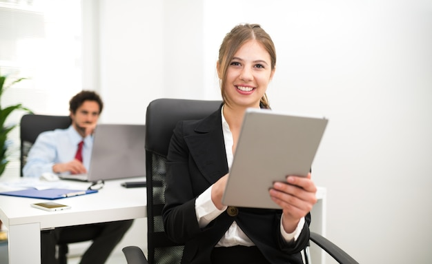 Portrait of a smiling businesswoman using a tablet in her office