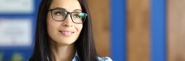 Portrait of smiling businesswoman with glasses in office.