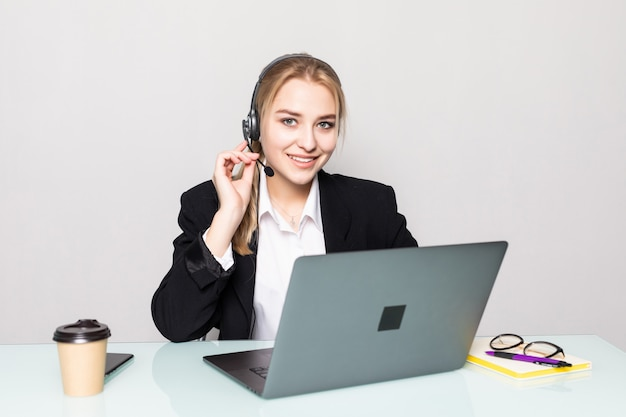Portrait of a smiling businesswoman with a headset on working in a call center in office