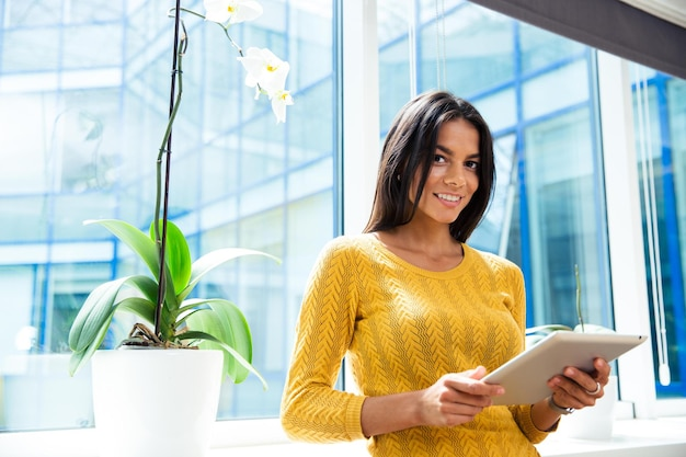 Portrait of a smiling casual businesswoman standing with tablet computer in office near window