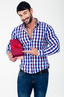 Portrait of a smiling casual man holding gift box isolated on a white wall