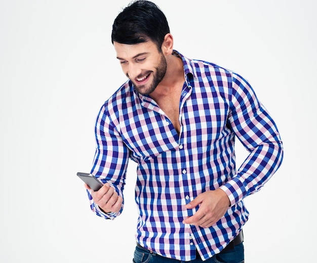 Portrait of a smiling casual man using smartphone isolated on a white wall