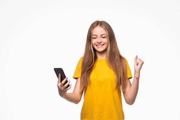Ritratto di una donna casuale sorridente che tiene smartphone sopra il muro bianco