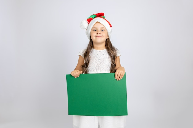Portrait of a smiling caucasian girl in white dress and christmas gnome hat holding green empty bann...