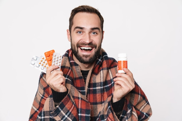 Portrait of smiling caucasian guy wrapped in blanket holding bunch of tablets due to flu isolated over white wall