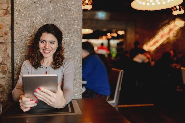 Портрет улыбается кавказской молодой женщины в ресторане, держа планшет.