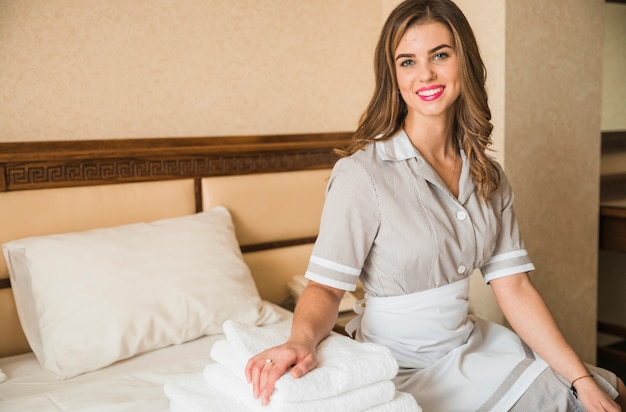 Portrait of a smiling chambermaid sitting on bed with stacked of soft folded towel