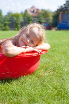 Portrait of smiling charming little girl have fun in the pool outdoors