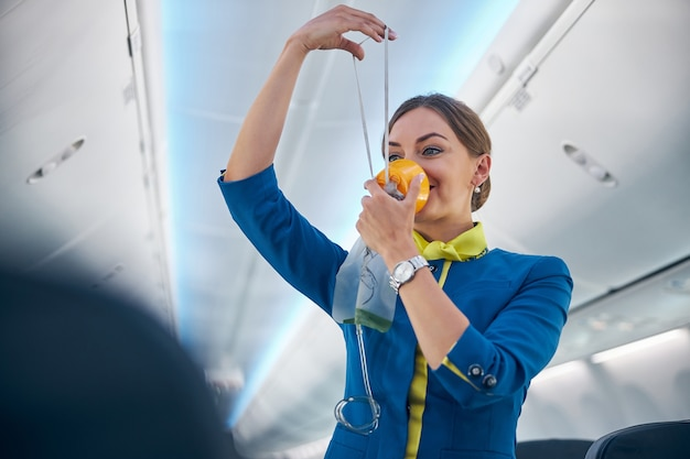 Portrait of smiling cheerful flight attendant demonstrating how grasping mask over nose and mouth while slip elastic band over head