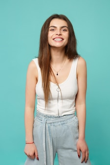 Portrait of smiling cheerful young woman in light casual clothes looking camera isolated on blue turquoise wall background in studio. people sincere emotions, lifestyle concept. mock up copy space.