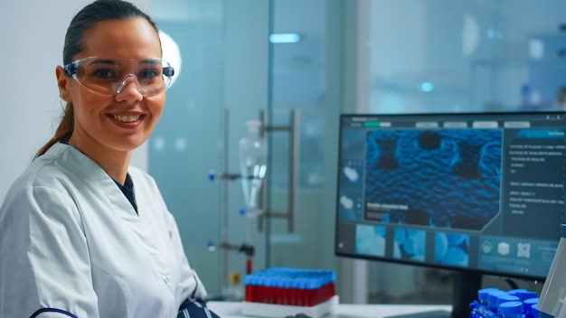 Portrait of a smiling chemist wearing safety glasses in lab looking at camera. team of scientists doctors examining virus evolution using high tech and chemistry tools for scientific research, vaccine