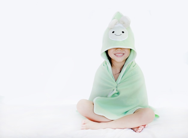 Portrait of smiling child girl after bath covered head and eyes with towel on white backgr