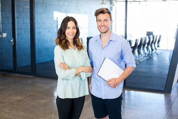 Portrait of smiling colleagues standing in office with arms crossed and holding document