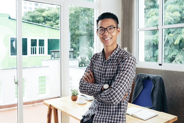 Portrait of smiling confident entrepreneur crossing arms and looking at camera when leaning on desk