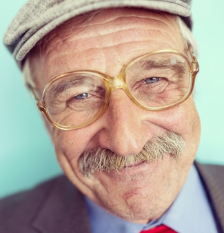 Portrait of a smiling and confident mature man with mustache, wrinkles and grey hair smiling
