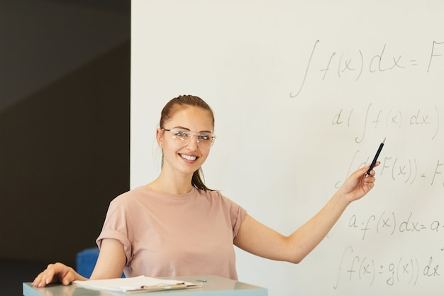 Portrait of smiling confident student girl in eyeglasses pointing at math formula while explaining solution at class