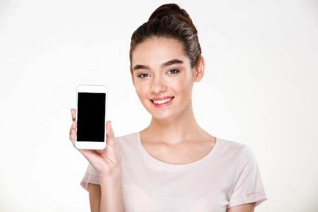 Portrait of smiling content woman demonstrating efficient cell phone showing screen