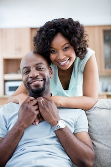 Portrait of smiling couple embracing each other in living room