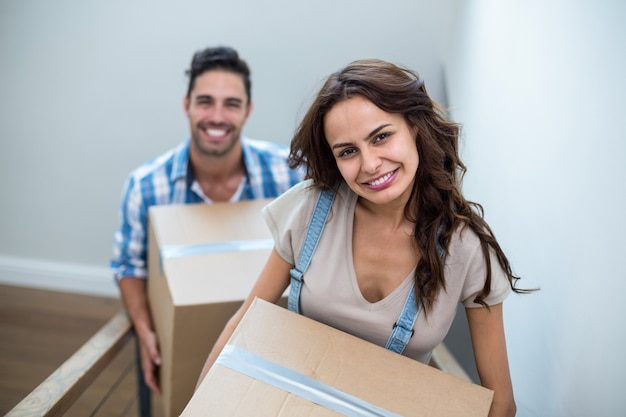 Portrait of smiling couple holding cardboard boxes while climbing steps