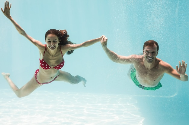 Portrait of smiling couple holding hands while swimming