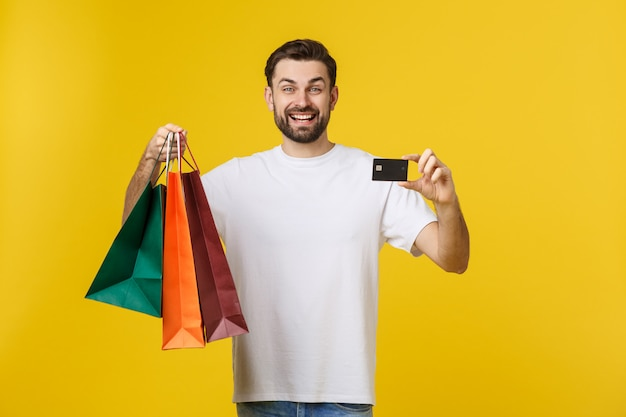 Portrait of smiling couple holding shopping bags and credit card isolated on yellow.