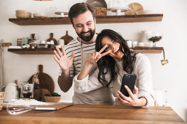 Portrait of smiling couple man and woman 30s wearing aprons hugging together and holding smartphone while cooking in kitchen at home