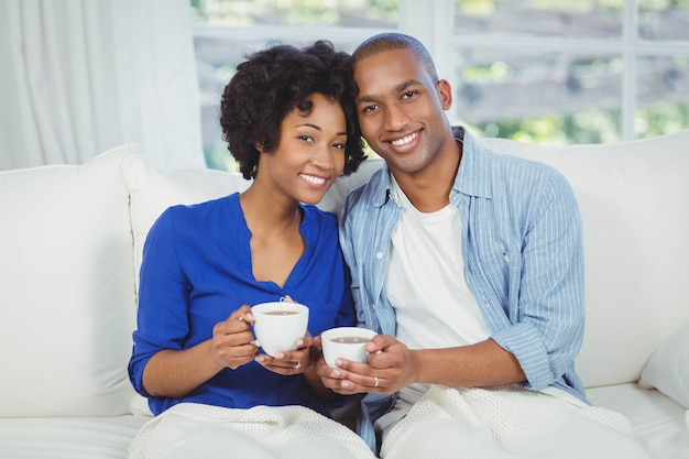 Portrait of smiling couple on the sofa holding cups
