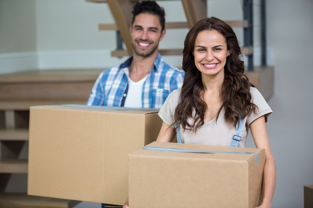 Portrait of smiling couple with cardboard boxes
