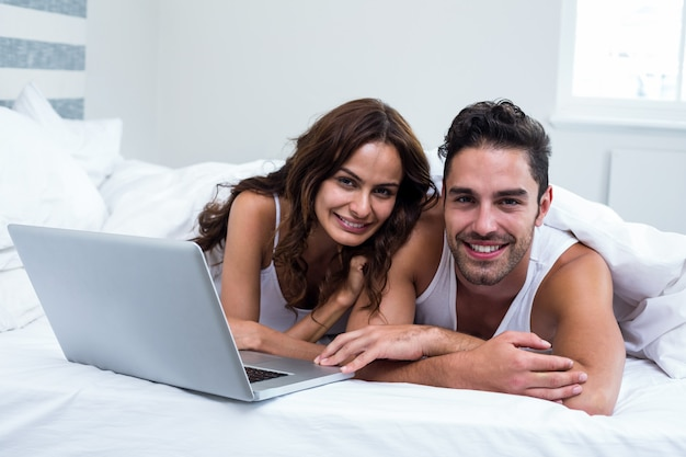 Portrait of smiling couple with laptop while lying under blanket