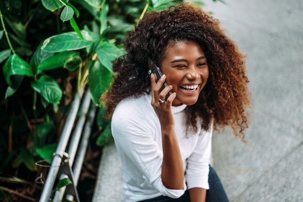 Portrait of smiling curly hair woman talking on phone.