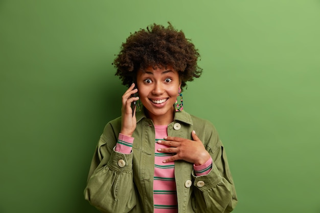 Portrait of smiling curly haired woman talks via cellphone, enjoys pleasant great conversation, wears fashionable jacket, poses