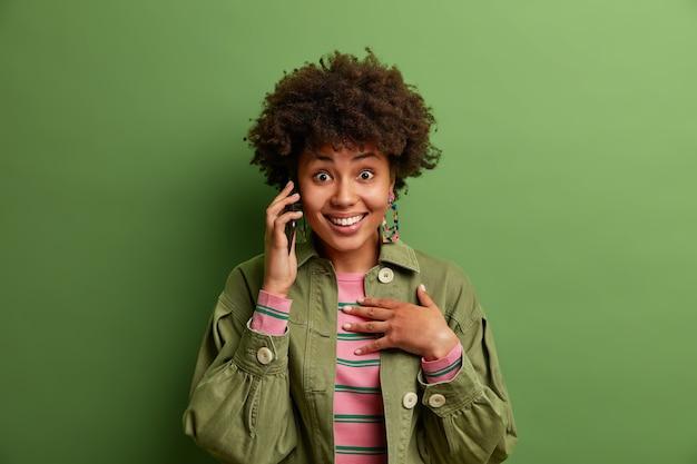 Ritratto di sorridente donna dai capelli ricci parla tramite cellulare, gode di una piacevole conversazione, indossa giacca alla moda, pose
