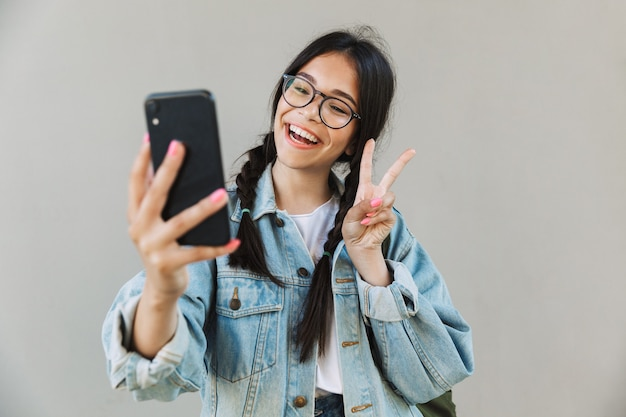 Portrait of a smiling cute beautiful girl in denim jacket wearing eyeglasses isolated over gray wall using mobile phone take a selfie showing peace.
