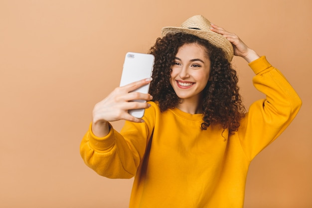 Portrait of a smiling cute curly student woman making selfie photo on smartphone isolated on a beige background.