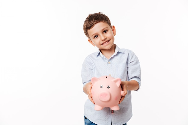 Portrait of a smiling cute little kid holding piggy bank