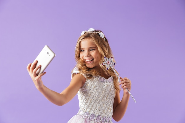 Portrait of a smiling cute pretty girl dressed in a princess dress isolated over violet wall, holding magic wand, taking a selfie