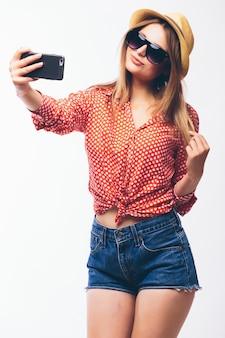 Ritratto di una donna carina sorridente che fa selfie foto sullo smartphone isolato su uno sfondo bianco
