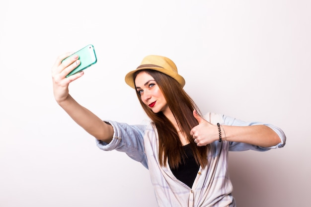 Portrait of a smiling cute woman making selfie photo on smartphone on a white