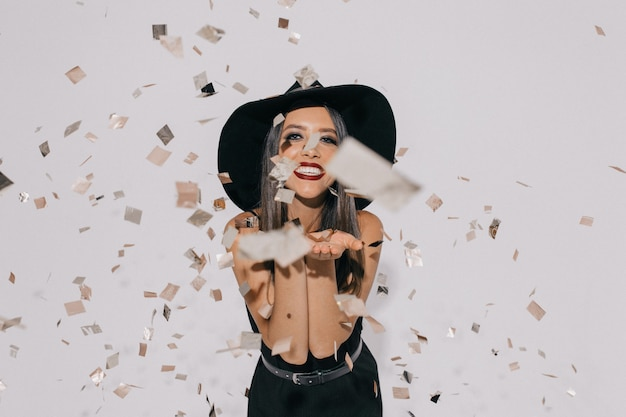 Portrait of smiling dancing girl in trendy black dress and hat. long-haired young female model fooling around in room with confetti.