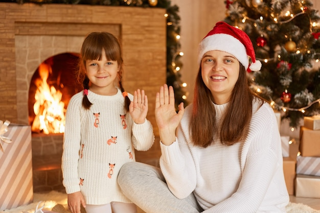 Portrait of smiling dark haired female wearing white sweater and santa claus hat posing with her little daughter, looking at camera and waving hands, merry christmas.