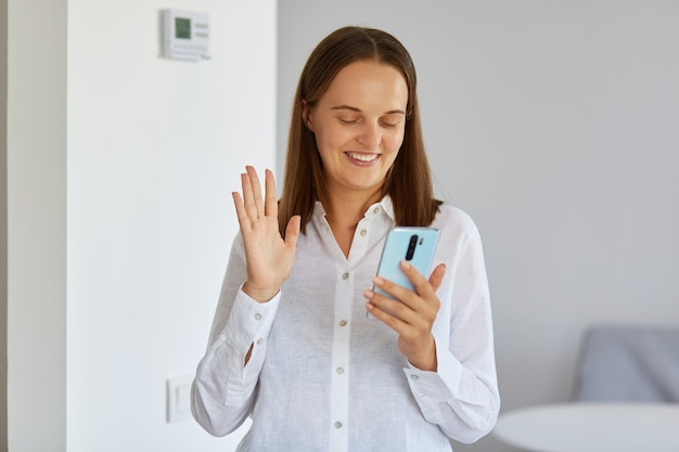 Portrait of smiling dark haired young adult female wearing white shirt standing at home with phone in hands, having video call, waving hand to device camera.