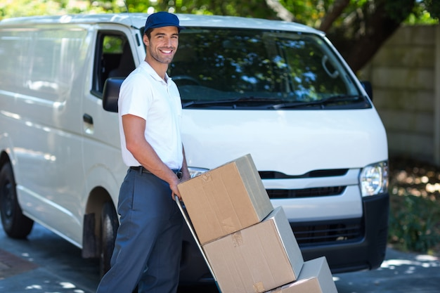 Portrait of smiling delivery man carrying cardboard boxes