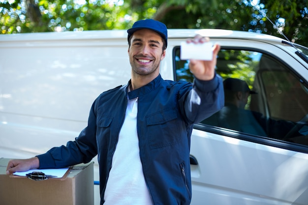 Portrait of smiling delivery man showing business card