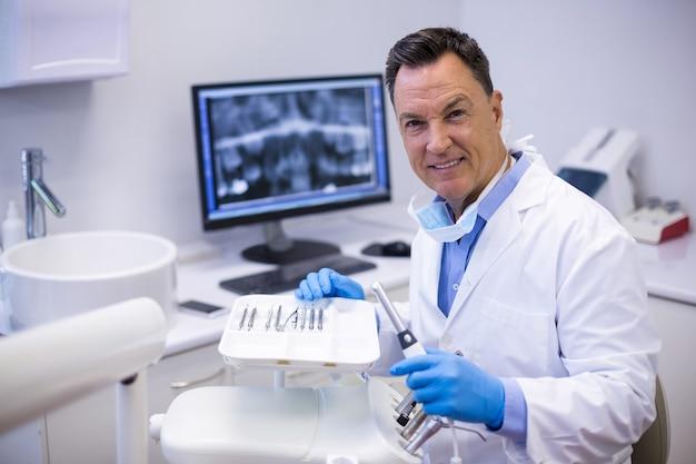 Portrait of smiling dentist holding dental hand piece