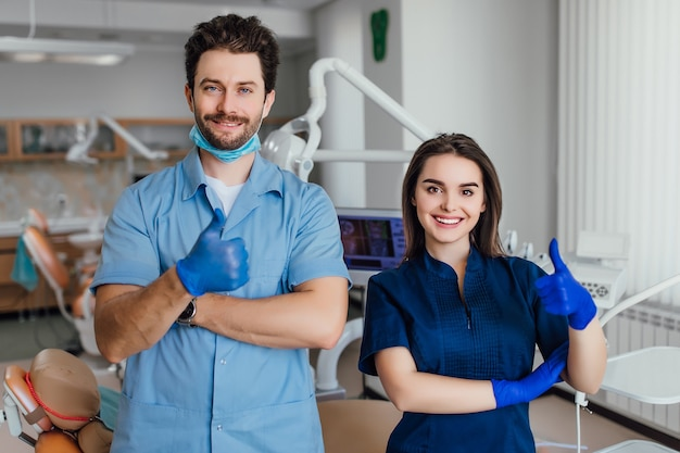 Portrait of smiling dentist standing with arms crossed with her colleague, showing okay sign.