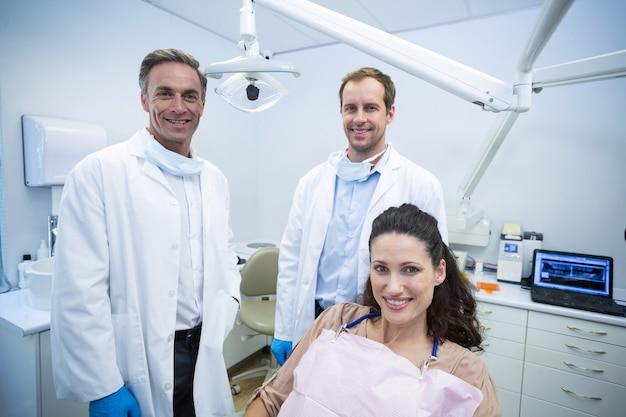 Portrait of smiling dentists and female patient