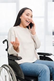 Portrait of a smiling disabled young woman sitting on wheel chair talking on mobile phone shrugging